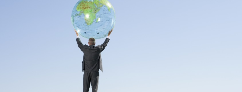 Businessman standing next to globe